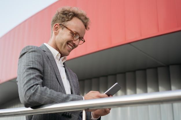 Homme souriant tenant une communauté de messagerie texte sur téléphone portable en ligne lisant des nouvelles dans la rue