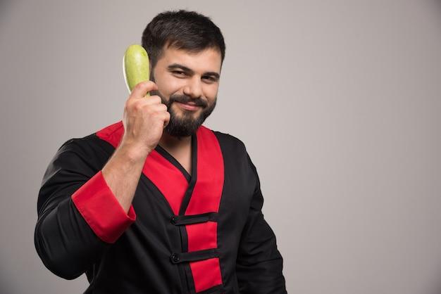 Homme souriant tenant dans la main des courgettes fraîches.