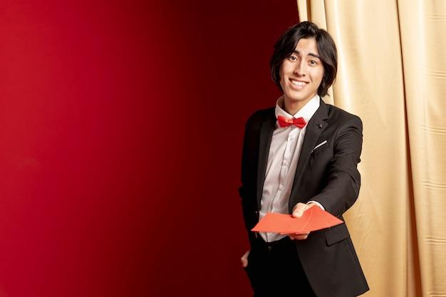 Homme souriant tenant des enveloppes pour le nouvel an chinois avec espace de copie