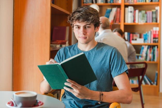 Homme souriant, tenant le livre dans les mains