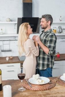 Homme souriant, tenant mains, à, femme joyeuse, près, table, à, verre vin, et, plaque