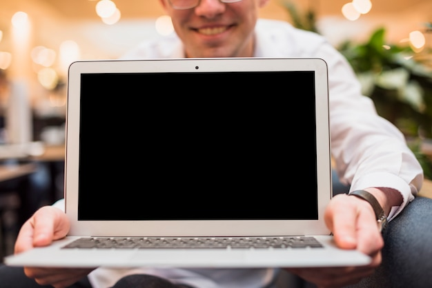 Homme souriant tenant un ordinateur portable ouvert avec écran noir