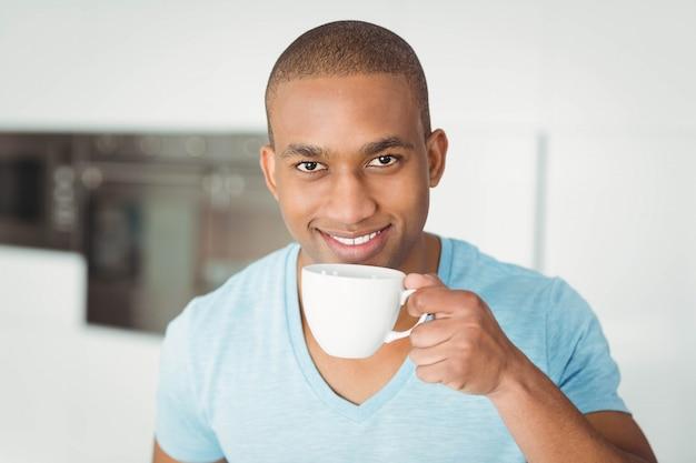 Homme souriant tenant une tasse dans la cuisine