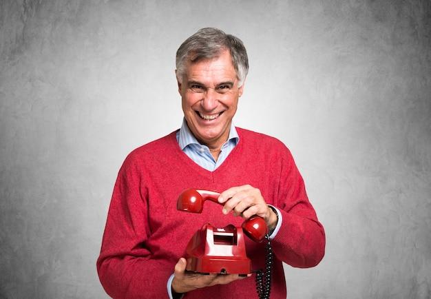 Homme souriant, tenant un téléphone vintage