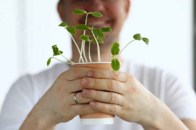 Homme souriant tenir le pot avec des pousses vertes closeup