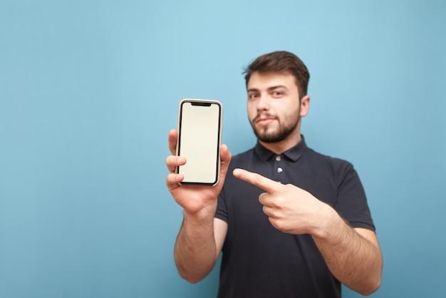 Homme souriant tient un smartphone dans ses mains et montre son doigt sur un écran blanc sur bleu