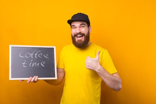 Un homme souriant tient un tableau noir avec l'heure du café écrite dessus