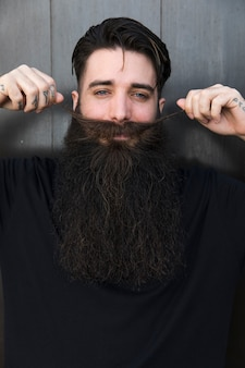 Homme souriant tirant sa moustache