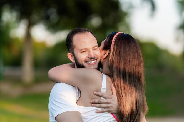 Homme souriant tout en embrassant une femme dans un parc