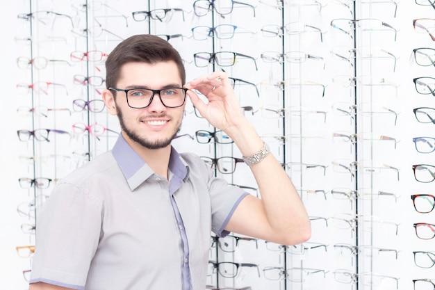 Homme souriant tout en essayant des lunettes dans le magasin