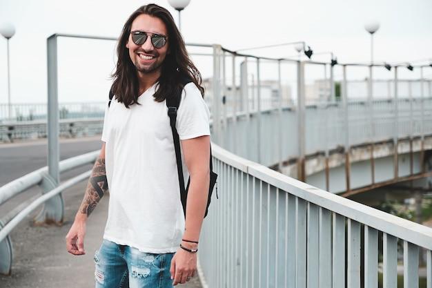 Homme souriant traîner, marcher dans la ville