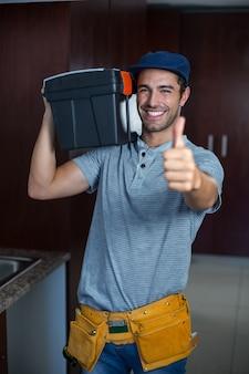 Homme souriant, transportant une boîte à outils, tout en montrant les pouces vers le haut