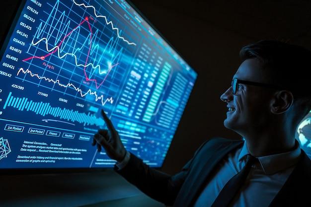 L'homme souriant travaillant sur un écran bleu de capteur