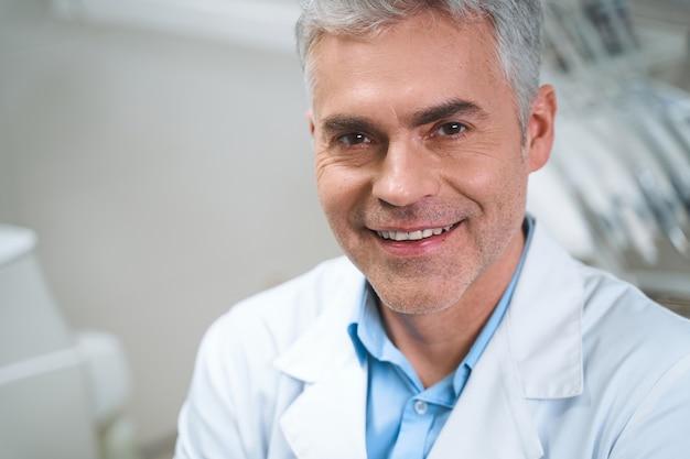 Un homme souriant en uniforme blanc est assis dans un bureau moderne et attend le traitement des patients