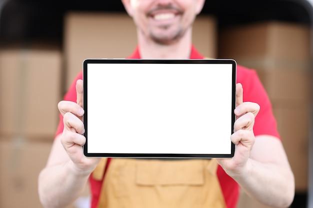 Un homme souriant en uniforme tient une tablette avec un écran blanc en arrière-plan de boîtes en carton