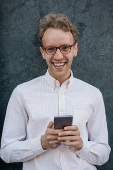 Homme souriant utilisant une application mobile pour les achats en ligne indépendant prospère tenant un smartphone dans la rue