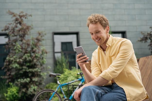 Homme souriant utilisant un téléphone portable faisant des achats en ligne un jeune indépendant heureux reçoit un paiement en ligne