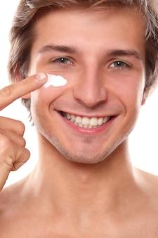 Homme souriant, utilisation, crème faciale
