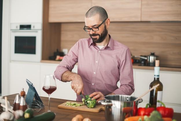 Homme souriant avec verre de vin cuisson ragoût de légumes à l'aide de la tablette. il coupe un brocoli, une courgette, un poivron rouge, un oignon et d'autres légumes.
