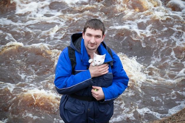 Homme souriant en veste bleue avec chaton blanc dans sa poitrine debout contre le courant de la surface de l'eau.