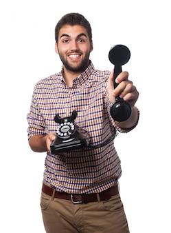 Homme souriant avec un vieux téléphone