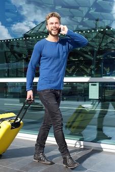Homme souriant voyageant avec valise et téléphone portable