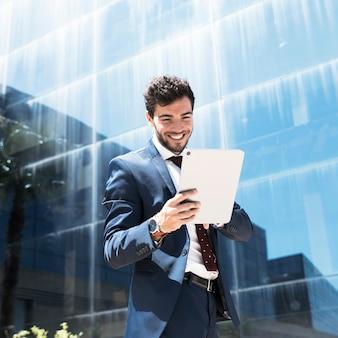 Homme souriant vue de côté en regardant tablette