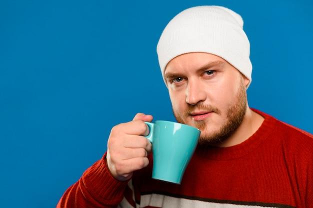 Homme souriant vue de face, levant une tasse de café