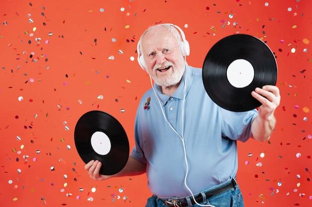 Homme souriant vue de face tenant des disques de musique