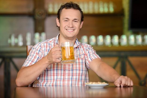 Un homme sourit et s'assied avec un verre de bière.
