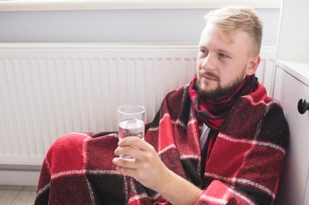 Homme sous couverture tenant un verre d'eau