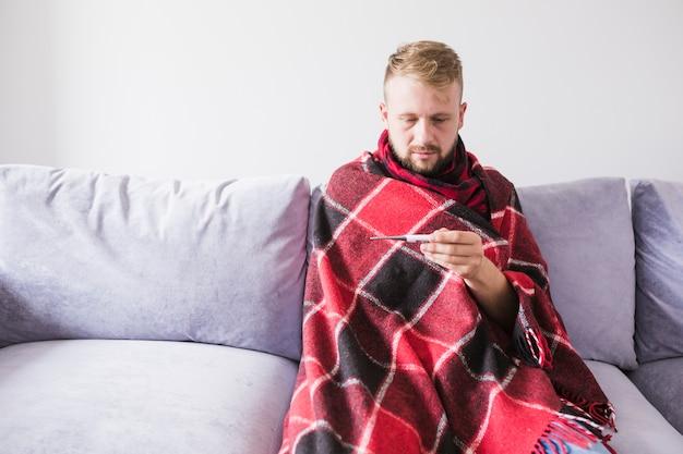 Homme sous couverture avec thermomètre