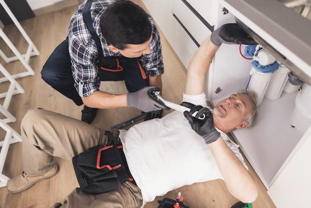 L'homme sous l'évier pour réparer la panne.