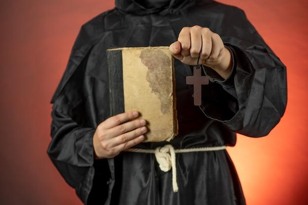 Un homme en soutane monastique tient un vieux livre et un crucifix dans ses mains