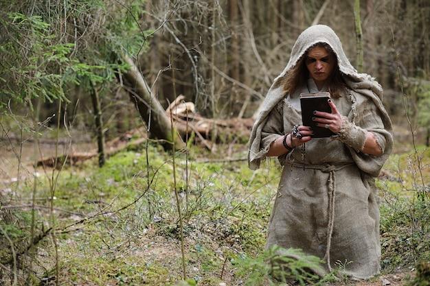 Un homme en soutane passe un rituel dans une forêt sombre avec une boule de cristal et un livre