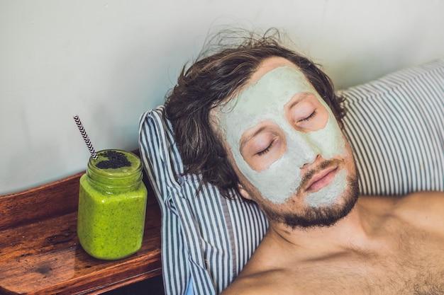 Homme de spa appliquant un masque d'argile verte pour le visage. soins de beauté. smoothie vert frais à la banane et aux épinards au cœur de graines de sésame. l'amour pour un concept d'aliments crus sains. concept de désintoxication