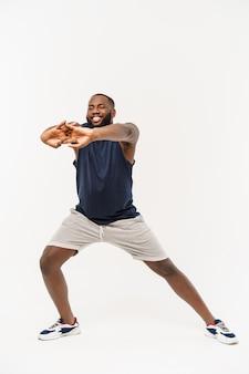 Homme de sport africain exerçant et s'étendant sur blanc