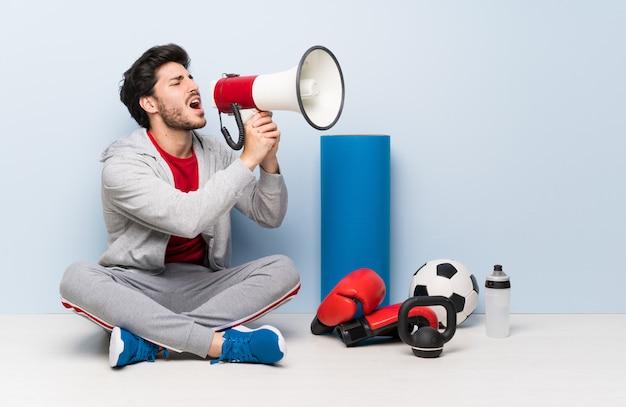 Homme de sport assis sur le sol en criant à travers un mégaphone