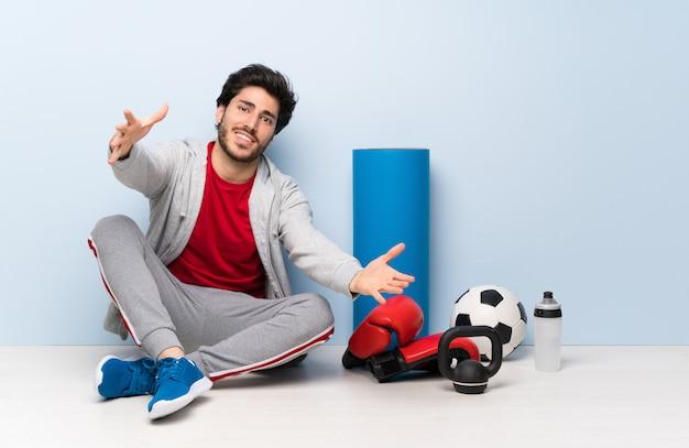 Homme de sport assis sur le sol présentant et invitant à venir avec la main