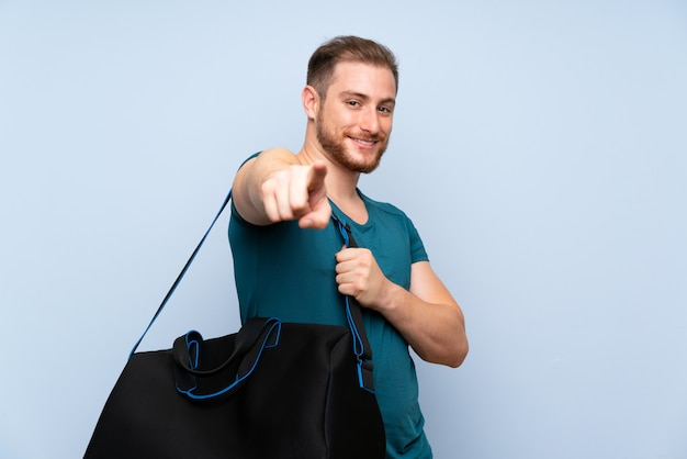 Un homme de sport blond sur un mur bleu pointe le doigt vers vous avec une expression confiante
