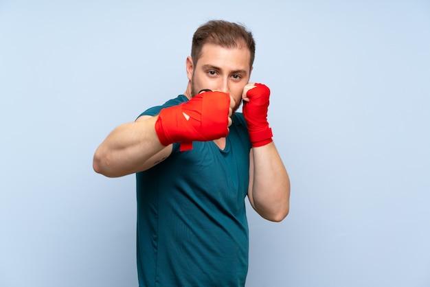 Homme de sport blonde sur un mur bleu dans des bandages de boxe