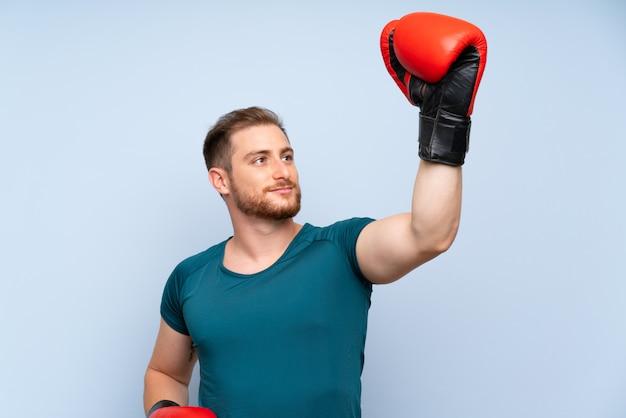 Homme de sport blonde sur un mur bleu avec des gants de boxe