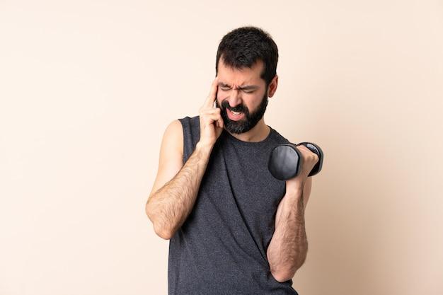 Homme de sport caucasien avec barbe faisant de l'haltérophilie sur un mur isolé avec des maux de tête
