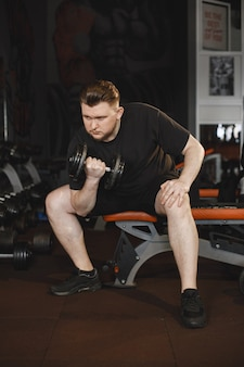 Homme de sport dans la salle de gym. un homme effectue des exercices. mec en t-shirt