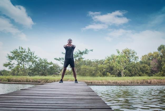 Homme de sport exercice et ver vers le haut sur le pont avec la rivière