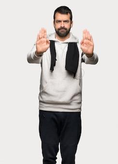 Homme de sport faisant geste d'arrêt pour déçu avec un avis sur fond gris isolé