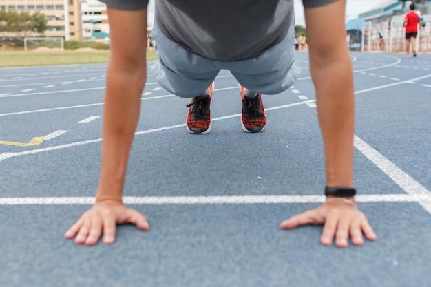 Homme de sport faisant des push ups exercice sur la piste de course bleue au stade.