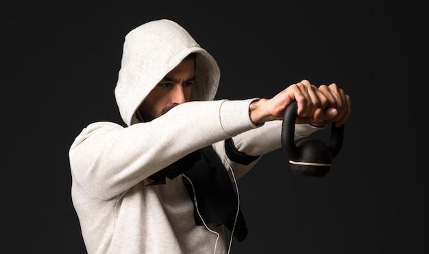 Homme de sport sur fond sombre faisant de l'haltérophilie
