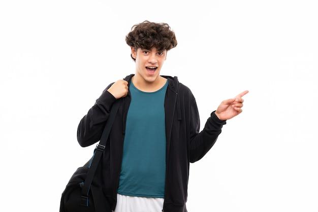 Homme de sport sur mur blanc isolé surpris et pointant le doigt sur le côté