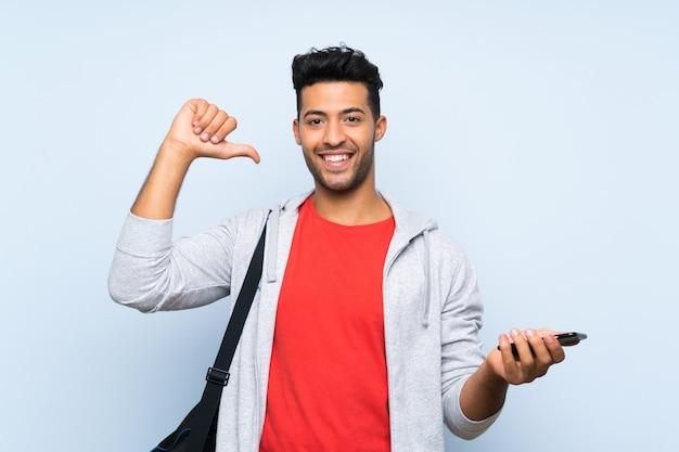 Homme de sport sur mur bleu isolé fier et satisfait
